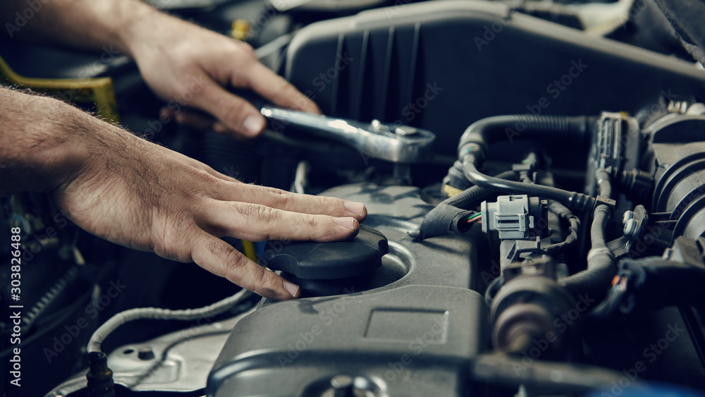 Fototapety, obrazy: Hand von Mechatroniker am Auto bei Inspektion