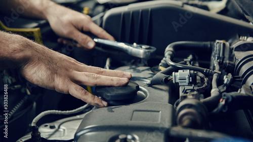 Hand von Mechatroniker am Auto bei Inspektion