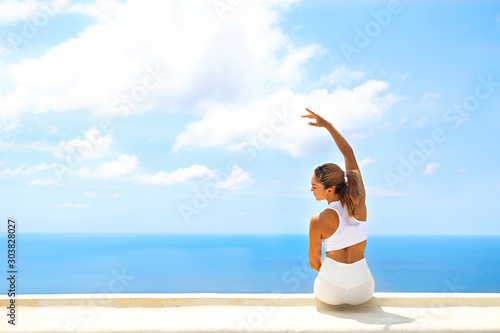Photo  Beautiful woman making stretching exercises in the beach