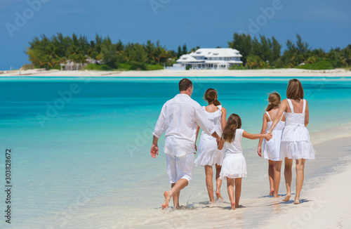 Fotomural  Happy Caucasian family in white walking on beach