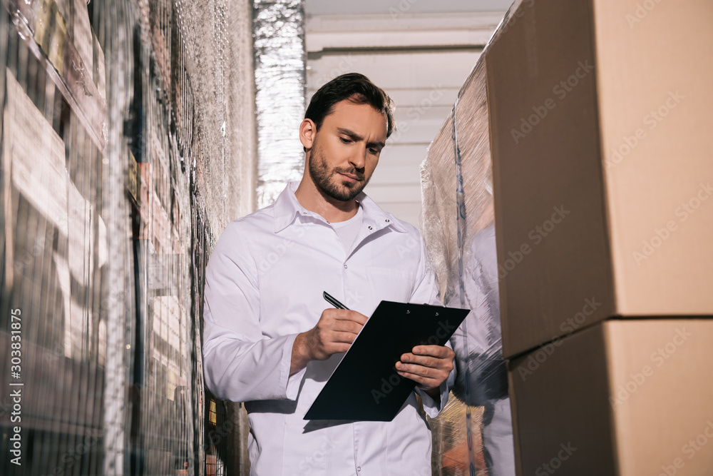 Fototapety, obrazy: concentrated storekeeper in white coat writing on clipboard in warehouse