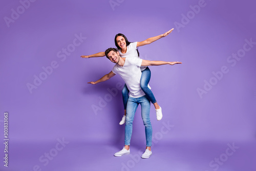 Full length body size photo of cheerful excited positive couple with her riding Wallpaper Mural