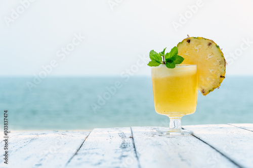 pineapple juice with sliced pineapple fruit on wooden table with abstract blue sea background , summer fruit drink concept - 303837474
