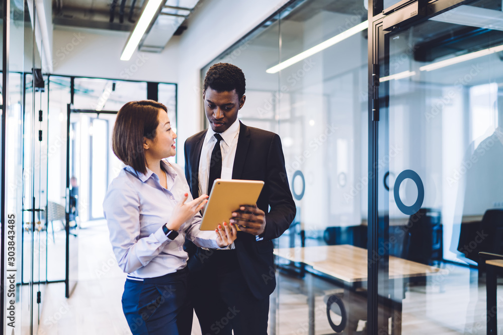 Fototapeta Businesspeople using tablet standing in office corridor