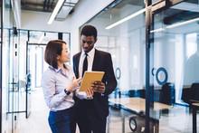 Businesspeople Using Tablet Standing In Office Corridor