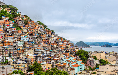 Fototapeta  Brazilian favelas on the hill with city downtown below at the tropical bay, Rio