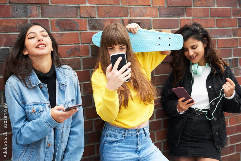 Fototapeta Three young women having fun with mobile phone