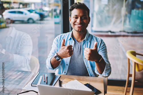 Half length portrait of handsome funny emotional hindu male person showing thumbs up while sitting at table in coffee shop Canvas Print