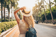 Chinese Tourist Walking In City Streets On Asia Vacation Tourism. Caucasian Beautiful Woman In Hat With Backpack Travel Lifestyle Concept. Walking Street, Green Palms And Highway In Sanya, Hainan.