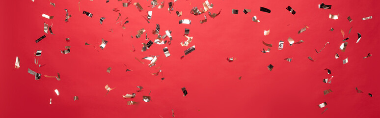 panoramic shot of christmas golden confetti isolated on red