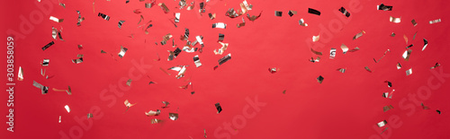 panoramic-shot-of-christmas-golden-confetti-isolated-on-red