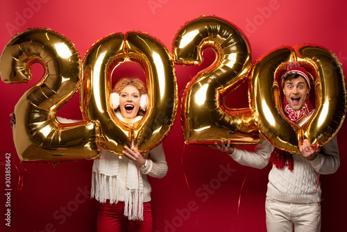 excited couple in winter outfit holding new year 2020 golden balloons, on red Wallpaper Mural