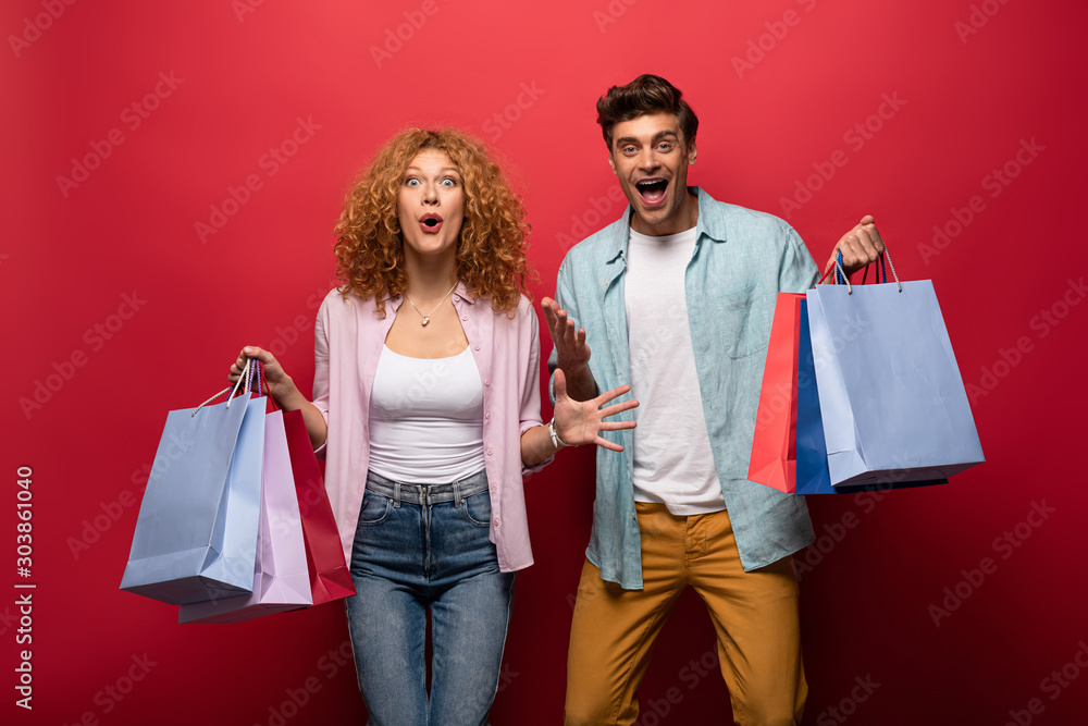 Fototapeta excited beautiful couple holding shopping bags, isolated on red