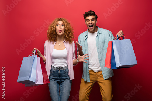 Fototapeta excited beautiful couple holding shopping bags, isolated on red obraz