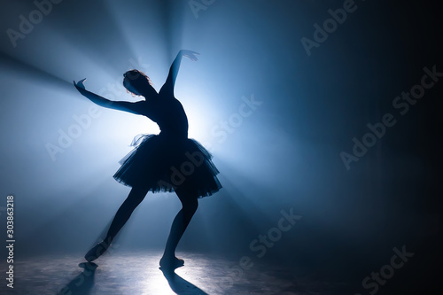 Obraz na plátně Ballerina in black tutu dress dancing on stage with magic blue light and smoke