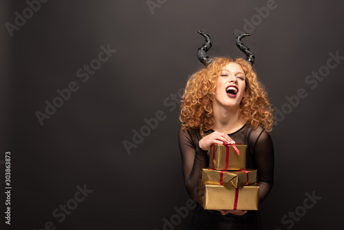 laughing woman in maleficent costume holding presents for halloween on black Tablou Canvas