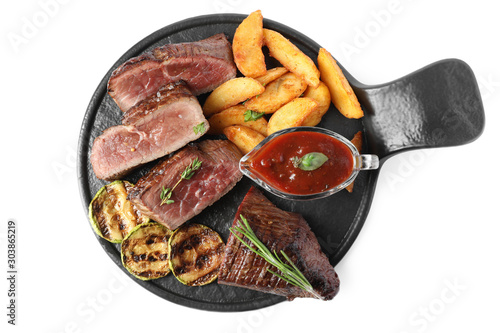 Delicious sliced beef tenderloin served with fried potatoes isolated on white, top view