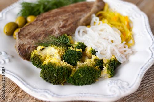 Photo Grilled cooked beef meat, broccoli, vegetable spaghetti shirataki, olives ketoge