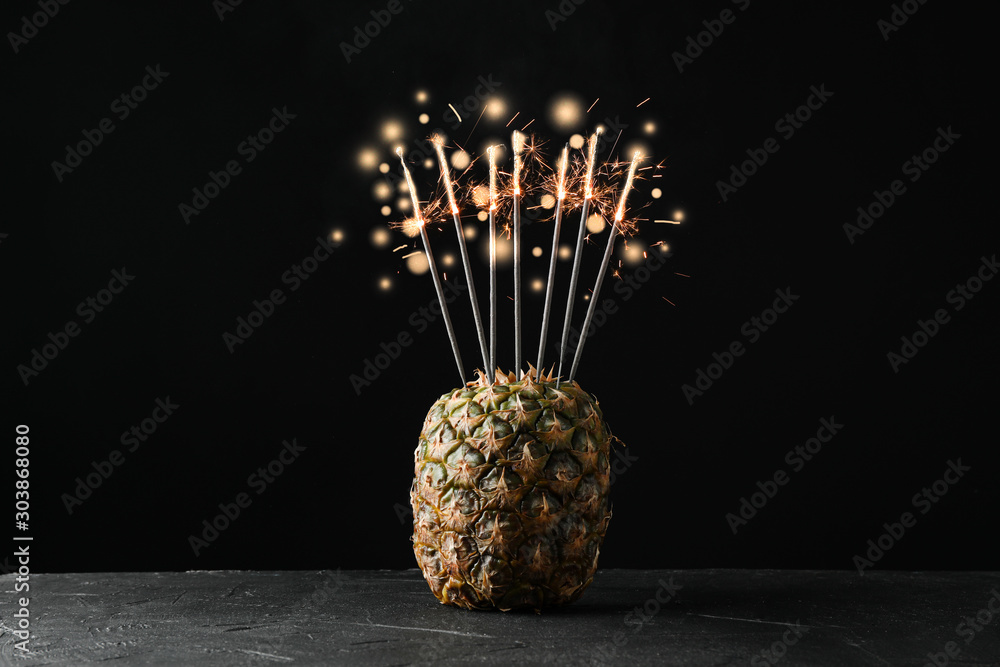 Fototapety, obrazy: Pineapple with burning sparklers on black background, space for text