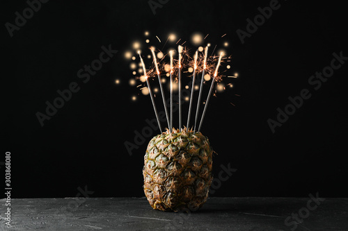 Pineapple with burning sparklers on black background, space for text - 303868080