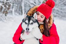 Beautiful Woman Hugging Her Dog Husky In Winter Park