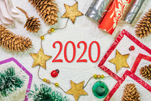 2020 Text Centered On Winter Holidays Flat Lay Composition Frame With Spruce Cones, Wrapping Paper, A Star String, Green Tinsel. Concept For New Year.
