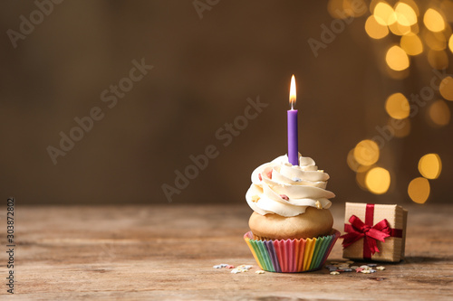 Birthday cupcake with candle and gift box on wooden table against blurred lights Wallpaper Mural