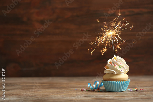 Photo  Birthday cupcake with sparkler on wooden table. Space for text