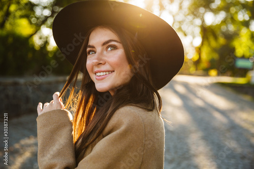 Image of attractive woman smiling while walking in green park outdoors