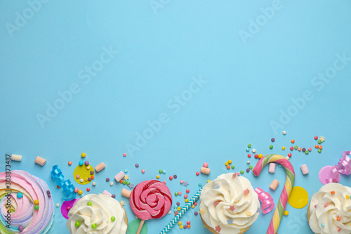 Foto op Plexiglas Snoepjes Flat lay composition with cupcakes on light blue background, space for text. Birthday party