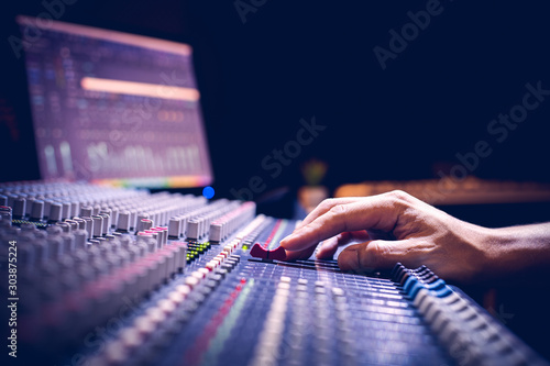 Photo male producer, sound engineer hands working on audio mixing console in broadcast