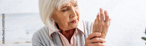 Fotografía panoramic shot of senior woman having pain in hand in apartment