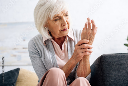 Fotografía senior woman having hand pain and sitting on sofa in apartment