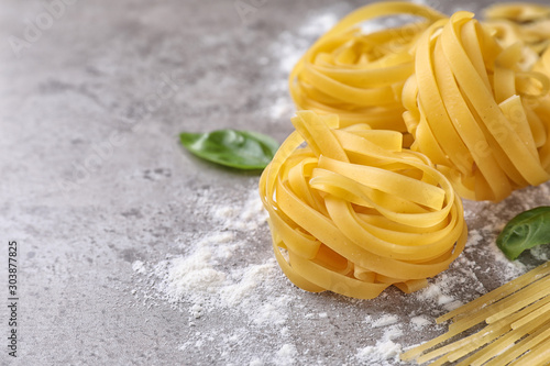 Fotografía  Uncooked tagliatelle pasta on grey table, closeup. Space for text