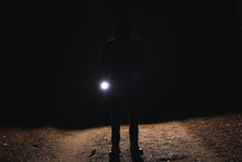 Silhouette Of Man With Bright Flashlight In Forest At Night