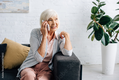Fotografía smiling senior woman sitting on sofa and talking on smartphone in apartment