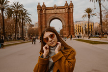 BARCELONA, SPAIN, January 17,2019.  Girl On The Background The Arch Of Triumph In Barcelona. Cute Young Girl Posing In Autumn Park. She Is Wearing Mustard Coat And Glasses.