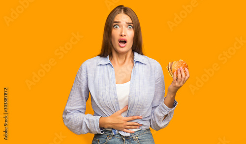 Pinturas sobre lienzo  Girl Holding Burger Having Stomachache Standing On Yellow Studio Background