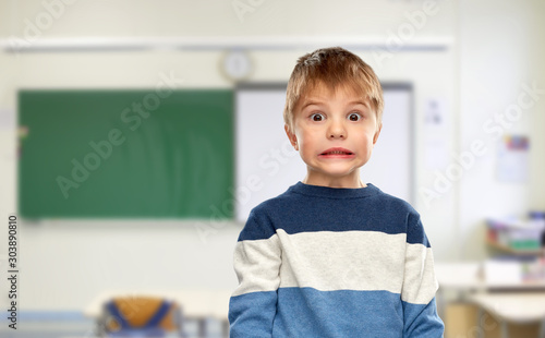 school, education and expressions concept - shocked little boy in striped pullov Canvas Print
