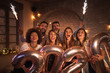 canvas print picture - Friends celebrating New Years Eve waving with sparklers and holding 2020 balloons