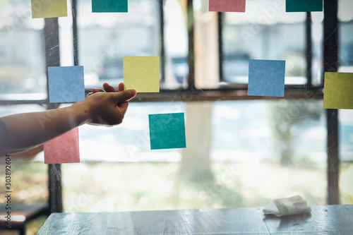 Fotografiet  Asian business man hand holding note paper meeting with new startup project use post it notes to share idea discussion and analysis data charts and graphs