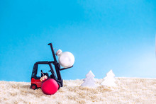 Selective Focus Of Christmas Ball By Forklift Machine On Sand Beach ,image For New Year Concept.