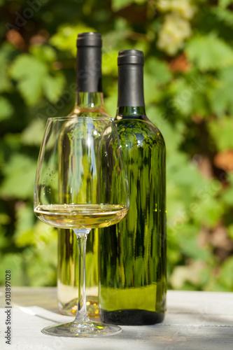 Fototapeta  White wine bottles and wineglass