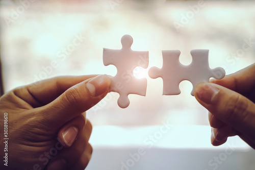 Obraz Closeup hand of business people connecting jigsaw puzzle with sunlight effect, Business solutions and represent team support and help concept, success and strategy concept - fototapety do salonu