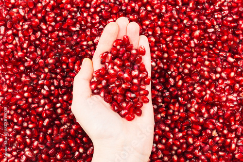 Red juicy pomegranate seeds in woman hand. - 303899008