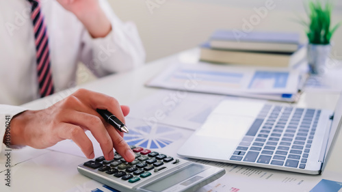 Fototapeta asian businessman or accountant working pointing graph discussion and analysis data charts and graphs and using a calculator to calculate  numbers.Business finances and accounting concept obraz