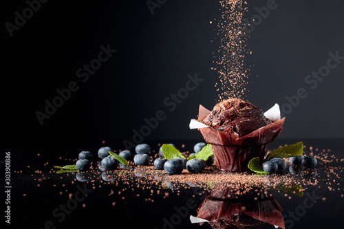 Fototapeta Chocolate muffin sprinkled with chocolate crumbs on a black reflective background