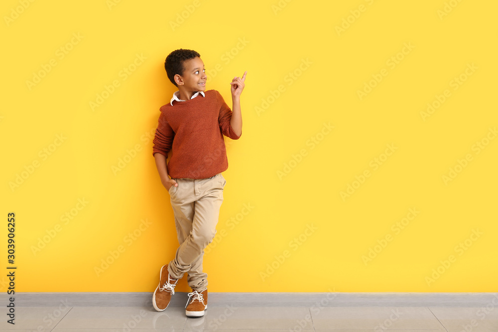Fototapeta Fashionable African-American boy in autumn clothes pointing at something while standing near color wall