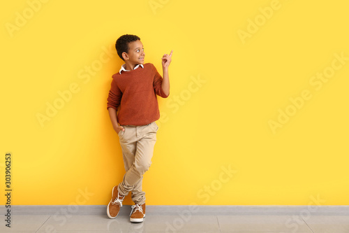 Fashionable African-American boy in autumn clothes pointing at something while standing near color wall