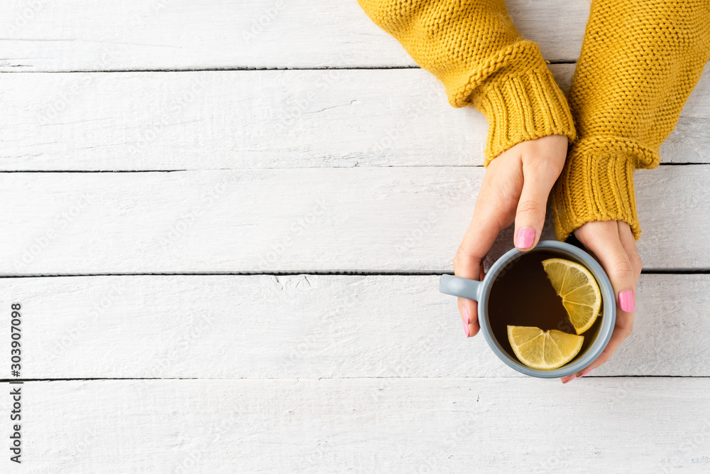 Fototapety, obrazy: Woman's hands in knitted sweater holding mug of tea with lemon on white wooden background with copyspace. Top view